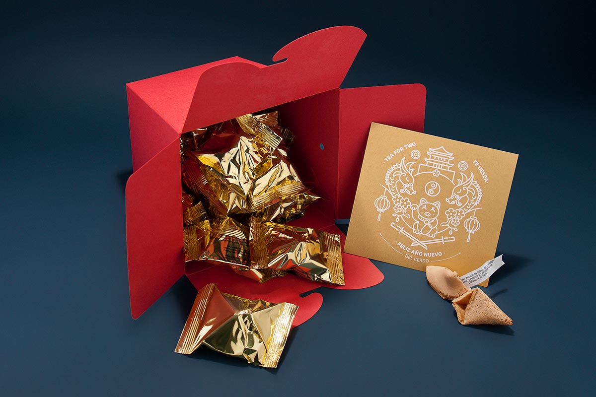 Red box of noodles full of fortune cookies with personalized messages as part of an intriguing packaging for New Year. Tea for two - package design.
