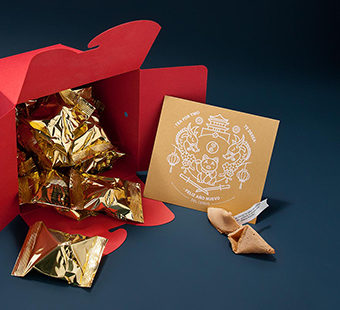 Mobile version of a red box of noodles full of fortune cookies with personalized messages as part of an intriguing packaging for New Year. Tea for two - package design.